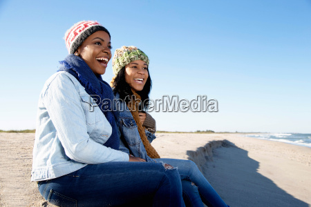 two female friends relaxing at beach
