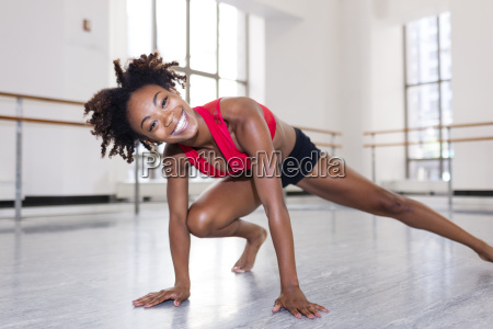 young woman in dance studio resting