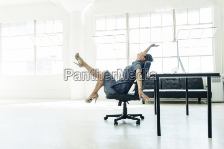 businesswoman excited on chair by office