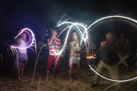 four adult friends celebrating with sparklers