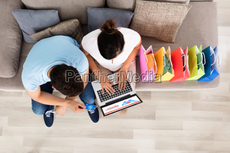 young couple sitting on sofa shopping