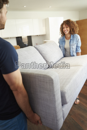 couple carrying sofa as they move