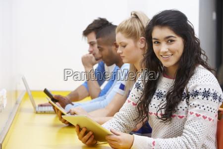 studerende studerer i klassevaerelset med digitale