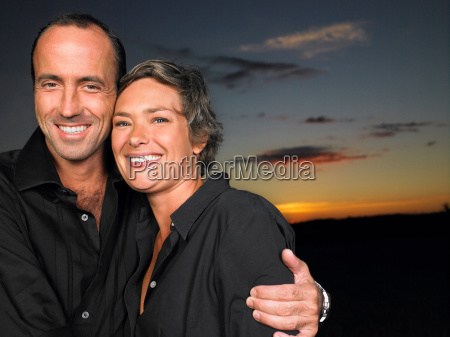 couple smiling in a field by