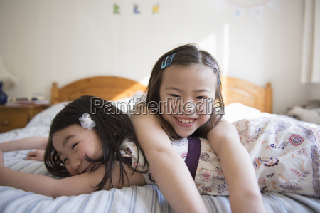 two young female friends lying on