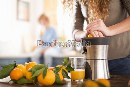 teenage girl juicing orange in kitchen