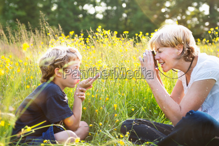 woman taking photograph of boy blowing