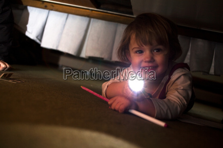 young girl playing with torch underneath