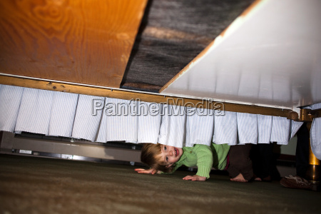 young girl hiding underneath bed