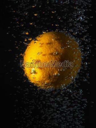 orange in bubbles black background