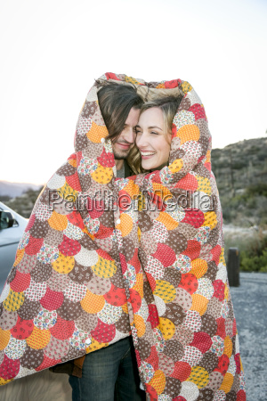 young couple wrapped in patchwork blanket