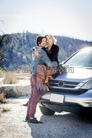 ungt par pa bil bonnet hugging