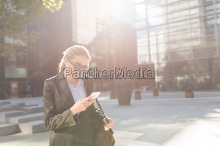young businesswoman outside city office reading