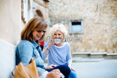 two mature female friends drinking coffee
