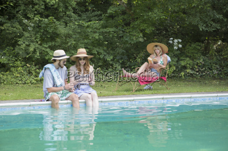 couple dipping legs into pool woman