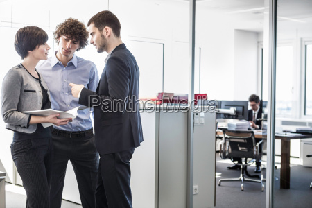 businesspeople, standing, in, office, looking, at - 19505550
