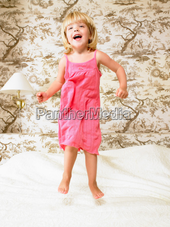 girl jumping on a bed