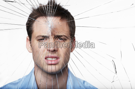 young man behind cracked glass