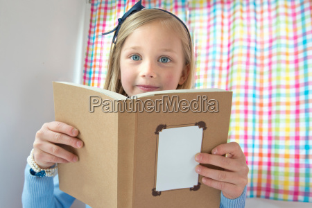 portrait of young girl reading book