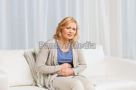 ulykkelig kvinde der lider af mavesmerter