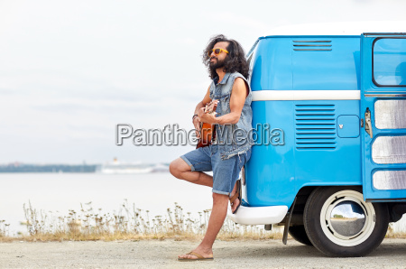 hippie mann spielt gitarre ueber minivan