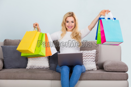 woman holding shopping bag with laptop