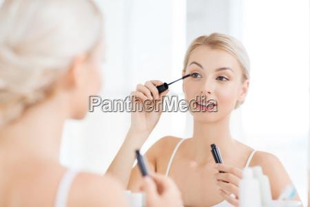 kvinde med mascara laegger make up