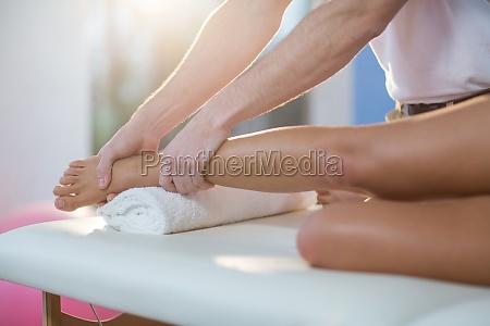 mand fysioterapeut giver knae massage til