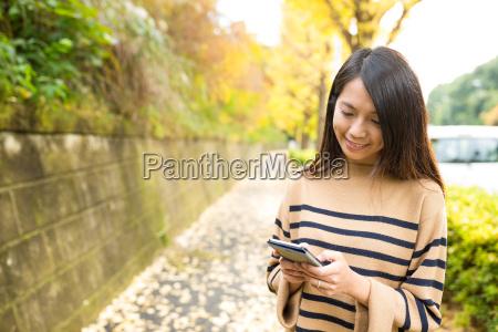 kvinde bruger mobiltelefon pa udendors park