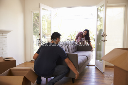 couple carrying sofa into new home