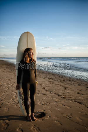 young woman with surfboard standing on