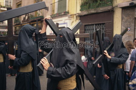 penitents bearing crosses in procession holy
