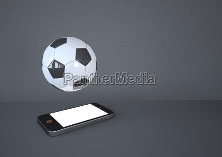 smartphone med fodbold pa gra baggrund