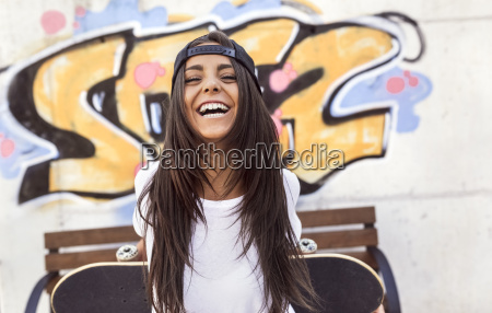 laughing young woman holding skateboard