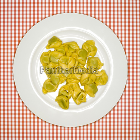 uncooked tortellini on plate elevated view