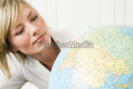ung forretningskvinde kigger pa kloden portraet
