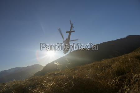 helikopter flyver over hills foran solen