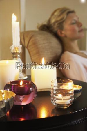 kvinde afslappende ved bord med taendte