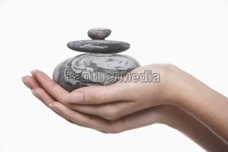 naerbillede af haender med bunke sten