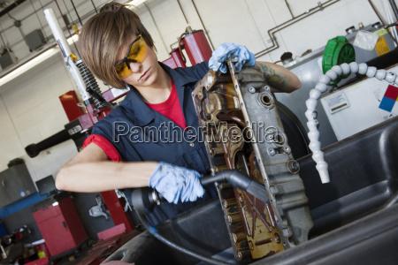 unge kvindelige mekaniker arbejder med svejsning
