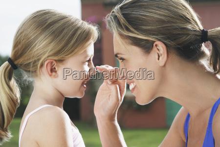 mor anvender solcreme til pigens naese
