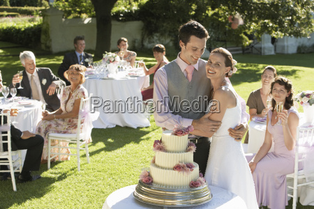 happy bride og brudgom foran bryllupskage
