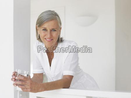 midaldrende kvinde med vandglas pa verandaen