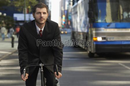 forretningsmand ridning cykel pa city street