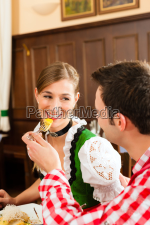 people in traditional bavarian tracht eating