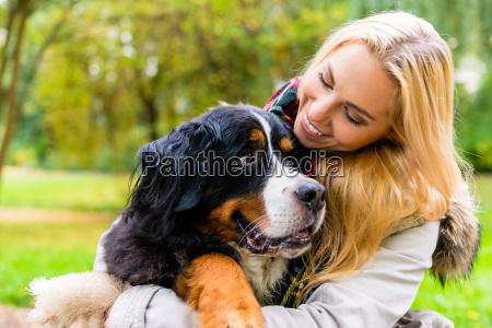 kvinde omfavner hendes hund i efterarsparken