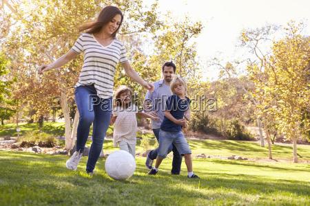 familie spiller fodbold i park sammen