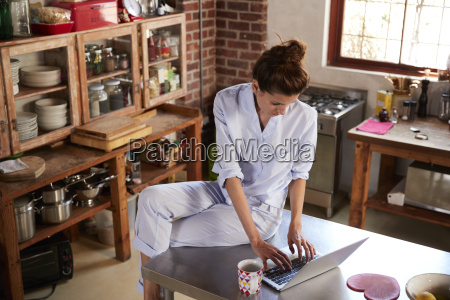 woman in pyjamas sits using laptop