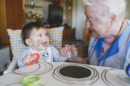 great grandmother playing with a baby