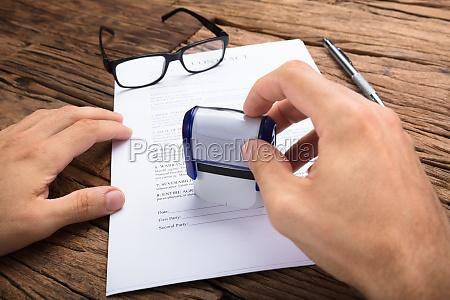 forretningsmand stempling kontraktpapir ved bordet